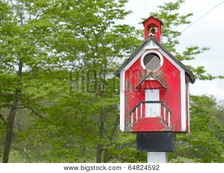 Red well worn birdhouse