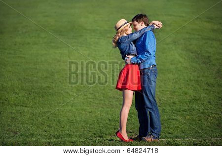 young couple embracing on a green lawn