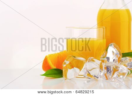 part view of juice in the glass and bottle with ice cubes and pieces of fresh oranges