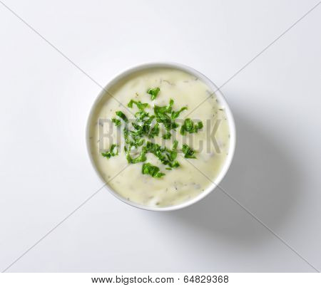 dressing sauce with chopped herbs