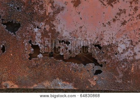 Brown paint on metal wall with corrosion.