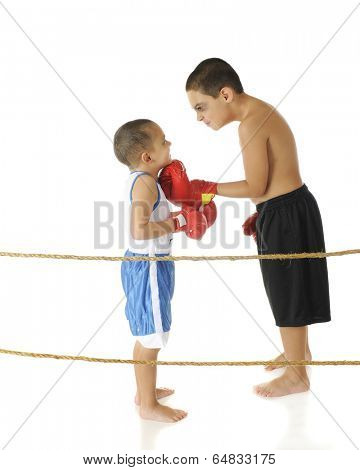 A tough-acting elementary boxer with a shiner threatening his preschool brother while standing behind boxing ring ropes.  On a white background.