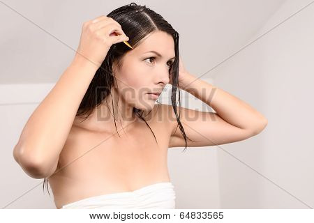 Young Woman Carefully Combing Lice Out Of Her Hair