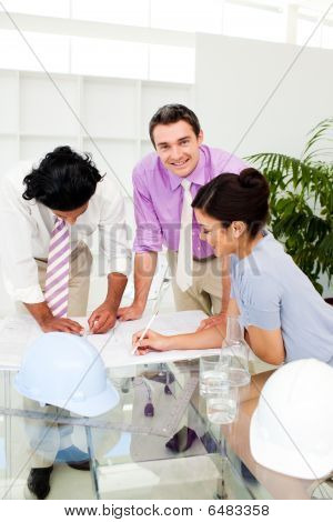 Multi-ethnic Architect Co-workers Reviewing Blueprints