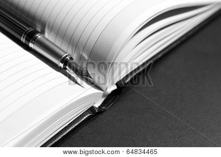 Pen on opened book on grey table, close up