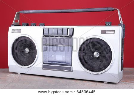 Retro cassette stereo recorder on table on red background