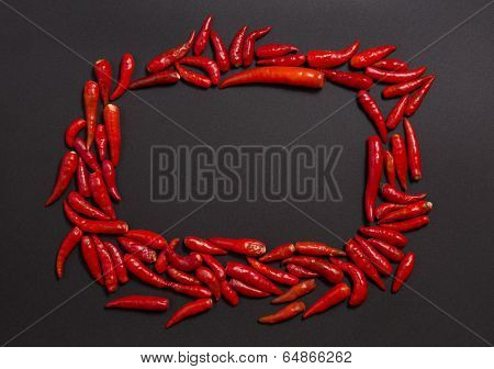 Frame made of non-stem red bird eye chili peppers on grey background