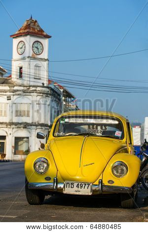 PHUKET TOWN, THAILAND - March 3: A retro Volkswagen car parked outside of the Promthep Clock Tower on March 3, 2014. The Clock Tower was build in 1914.