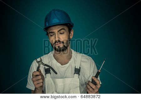 Attractive bearded young workman standing eyeing his tools holding up a pair pf pliers and a screwdriver as he decides which is best to use