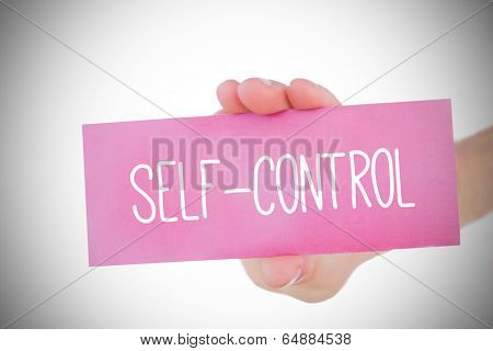 Woman holding pink card saying self control against white background with vignette