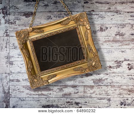 Gilt frame hanging with chain on grungy wooden background