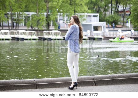 Happy young woman in white pants and a blue shirt walking in the summer park