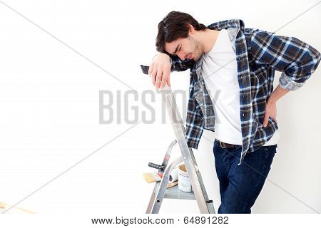 Young Man Suffering While Working On A Stepladder