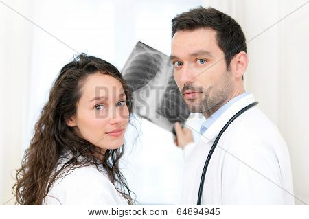 Young Doctor And Nurse Analysing Radiography