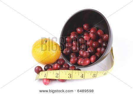 Cranberries Spilling Out Of A Black Bowl With Tape Measure