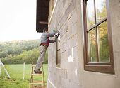 picture of trowel  - Plasterer spreading out plaster with trowel around the windows - JPG