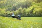 picture of wheelbarrow  - Young male farmer is relaxing in wheelbarrow on the green meadow - JPG
