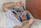 picture of obese man  - Man wearing a mask for treating sleep apnea - JPG