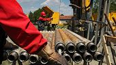 image of oil drilling rig  - Oil drilling rig workers lifting drill pipe - JPG