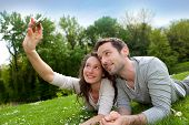 pic of selfie  - View of a Young couple taking selfie picture at the park - JPG