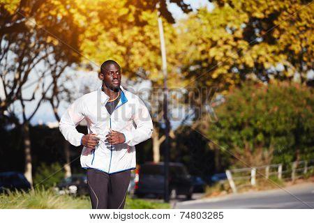 Dark skinned man running fast at sunny autumn evening