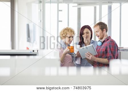 Businessman with female colleagues discussing over tablet PC in office