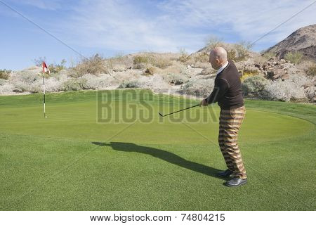Full length side view of senior male golfer swinging his club at golf course
