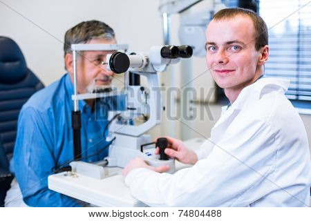 Optometry concept - senior man having his eyes examined by an eye doctor (color toned image; shallow DOF)