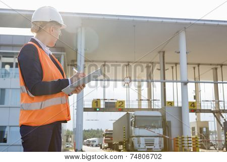 Female worker writing on clipboard while looking at trucks entering in shipping yard
