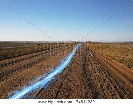 Blue streak of light on dirt road against clear sky