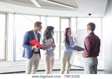 Businesswoman giving presentation to colleagues in creative office