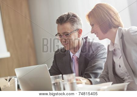 Businessman and businesswoman discussing while having lunch in office