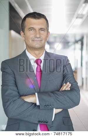 Portrait of middle-aged businessman standing with arms crossed in office