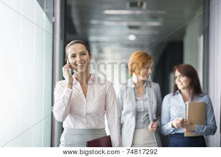 Young businesswoman on call with colleagues in background at office corridor