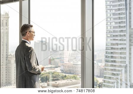 Side view of mature businessman looking through office window