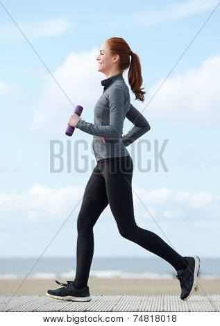 Happy Young Woman Jogging With Weights
