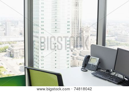 Desktop computer and landline phone on desk by glass window in office