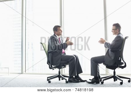 Full-length side view of businessmen discussing while sitting on office chairs by window