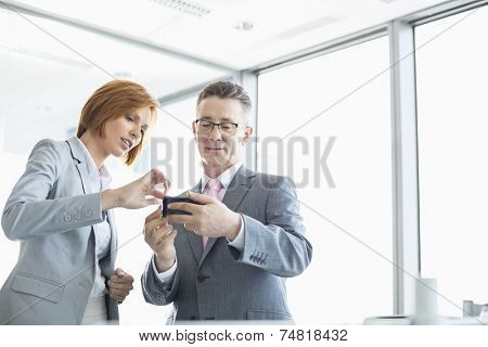 Businessman and businesswoman using cell people in office
