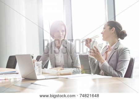 Young businesswomen having lunch at table in office