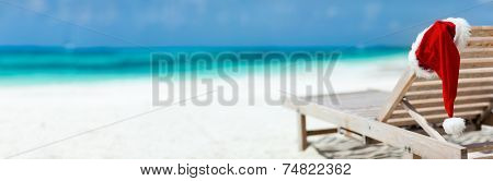 Panorama of sun lounger with Santa hat at beautiful tropical beach with white sand and turquoise water, perfect Christmas vacation