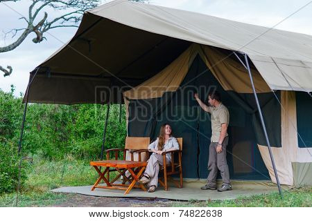 Young couple enjoying safari trip in front of their tent