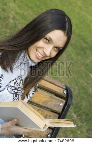 Young woman in a park with a book