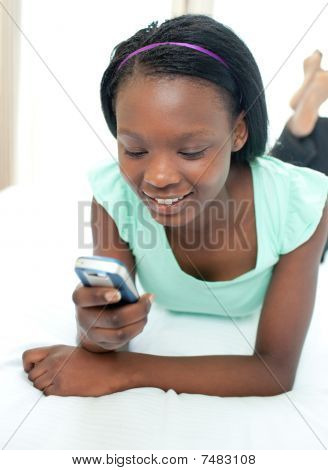 Cute Teen Girl Using A Mobile Phone Lying On Her Bed