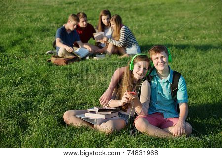 Teen Couple Sitting Outdoors