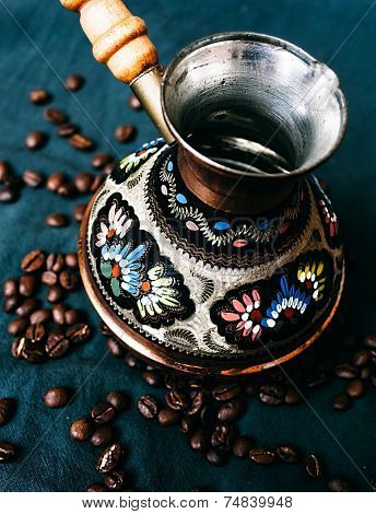 Decorative vintage Arabic Cezve for making Turkish coffee viewed high angle surrounded by whole roasted coffee beans below