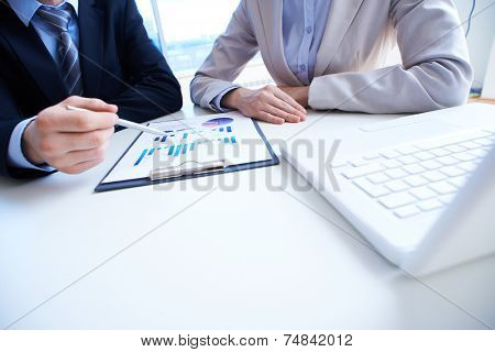 Close-up of male hand pointing at business document during explanation to female colleague near by