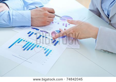 Close-up of female hand pointing at charts in business document during her report