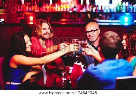 Friendly people toasting with alcoholic drinks while sitting in the bar