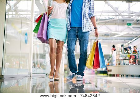 Legs of young couple shopping in trade center